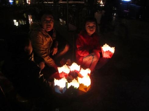 Hội An - Theo mẹ bán hoa đăng cho du khách mua thả xuống sông Hoài, mùa Đông 2012 - Hoi An, selling floating candles on Hoai River bank  - Photo: vandungsilk